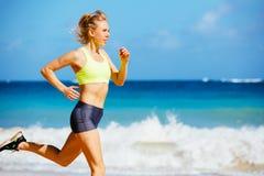 Funzionamento atletico della giovane donna sulla spiaggia Immagini Stock Libere da Diritti
