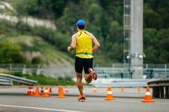 Funzionamento atletico maschio posteriore del corridore in strade con sicurezza dei coni di traffico Immagini Stock