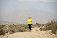 Funzionamento attraente della donna di sport sulla strada sporca della traccia della terra con il fondo del paesaggio della monta Immagine Stock