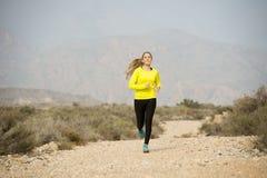 Funzionamento attraente della donna di sport sulla strada sporca della traccia della terra con il paesaggio della montagna del de Fotografie Stock