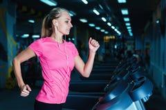 Funzionamento attraente della ragazza di forma fisica sulla pedana mobile a macchina Ragazza graziosa che fa allenamento alla pal Fotografie Stock