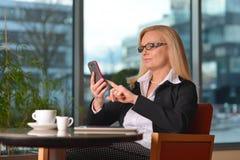 Funzionamento biondo di mezza età della donna di affari di Atractive fotografia stock