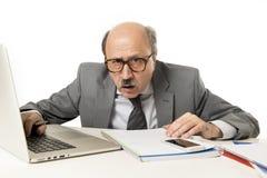 Funzionamento calvo dell'uomo 60s di affari sollecitato e frustrato allo scrittorio del computer portatile del computer di uffici fotografia stock