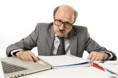 Funzionamento calvo dell'uomo 60s di affari sollecitato e frustrato allo scrittorio del computer portatile del computer di uffici immagini stock libere da diritti
