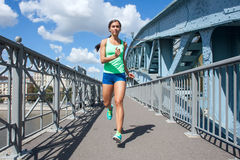 Funzionamento caucasico della donna sul ponte del metallo Immagini Stock
