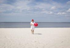 Funzionamento caucasico della donna sulla spiaggia sabbiosa con la palla rossa Fotografia Stock