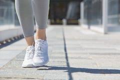 Funzionamento con le scarpe bianche all'aperto, luce solare della donna Fotografie Stock