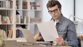 Funzionamento creativo dell'uomo sui documenti e sul computer portatile, lavoro di ufficio video d archivio