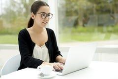Funzionamento d'uso di vetro della donna sul computer portatile Fotografie Stock Libere da Diritti