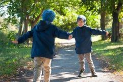 Funzionamento dei fratelli di gemelli monozigoti per abbracciarsi Immagine Stock