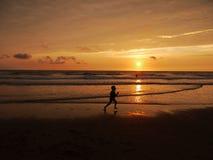 Funzionamento del bambino attraverso la spiaggia al tramonto Immagine Stock