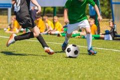 Funzionamento del calciatore con la palla spettatori nei precedenti Fotografie Stock