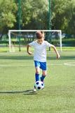 Funzionamento del calciatore del ragazzo con la palla Fotografia Stock