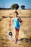 Funzionamento del cane e della donna in percorso rurale della campagna fotografia stock libera da diritti