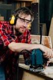 Funzionamento del carpentiere della fresatrice manuale della mano nell'officina di carpenteria falegname fotografie stock libere da diritti