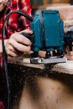 Funzionamento del carpentiere della fresatrice manuale della mano nell'officina di carpenteria falegname fotografie stock
