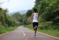 Funzionamento del corridore della donna alla traccia della foresta Immagini Stock Libere da Diritti