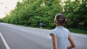 Funzionamento del corridore della donna e dell'uomo sulla strada aperta in campagna stock footage