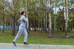 Funzionamento del corridore della donna nel parco Bello modello sportivo di forma fisica durante l'allenamento all'aperto Fotografia Stock
