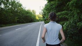 Funzionamento del corridore della donna sulla strada aperta in campagna video d archivio