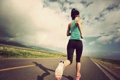 Funzionamento del corridore della giovane donna sulla bella strada immagini stock libere da diritti
