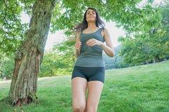 Funzionamento del corridore e dell'atleta femminile sul parco: benessere di allenamento di trotto Immagini Stock