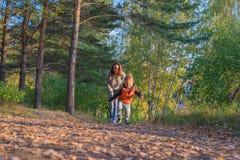 Funzionamento del figlio e della madre sul percorso nella foresta di autunno immagini stock libere da diritti