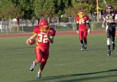 Funzionamento del giocatore di football americano con la palla Fotografia Stock