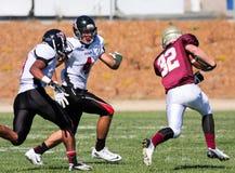 Funzionamento del giocatore di football americano con la palla durante il gioco Fotografie Stock