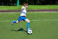 Funzionamento del giocatore di football americano del ragazzo con la palla su prato inglese verde Immagine Stock Libera da Diritti