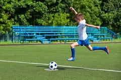 Funzionamento del giocatore di football americano del ragazzo con la palla su prato inglese verde Immagini Stock Libere da Diritti
