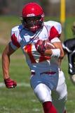 Funzionamento del giocatore di football americano della High School con la palla Fotografie Stock Libere da Diritti
