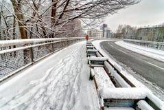 Funzionamento del pareggiatore lungo la strada nevosa curvy Fotografia Stock