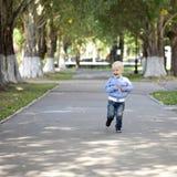 Funzionamento del ragazzino sul marciapiede nel parco di estate Immagini Stock Libere da Diritti