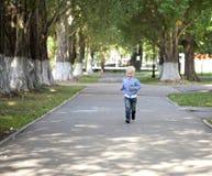 Funzionamento del ragazzino sul marciapiede nel parco di estate Fotografie Stock
