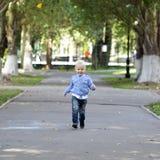 Funzionamento del ragazzino sul marciapiede nel parco di estate Fotografia Stock Libera da Diritti