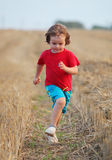 Funzionamento del ragazzo nel giacimento di grano con i vestiti rossi immagine stock libera da diritti
