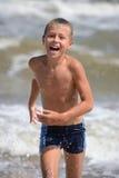 Funzionamento del ragazzo sulla spiaggia Immagini Stock