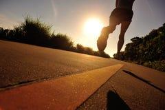 Funzionamento dell'atleta del corridore alla strada della spiaggia Fotografia Stock