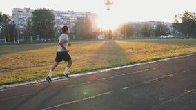 Funzionamento dell'atleta della corsa mista su una pista corrente per qualsiasi tempo da solo video d archivio