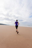 Funzionamento dell'atleta femminile alla spiaggia Immagini Stock Libere da Diritti