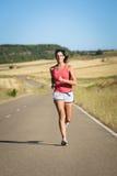 Funzionamento dell'atleta femminile in strada campestre Fotografia Stock