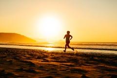 Funzionamento dell'atleta femminile sul tramonto alla spiaggia Immagine Stock Libera da Diritti