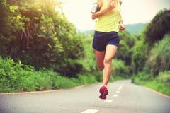Funzionamento dell'atleta sulla traccia della foresta concetto pareggiante di benessere di allenamento di forma fisica della donn Fotografia Stock Libera da Diritti