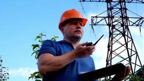 Funzionamento dell'elettrotecnico Parlando sul telefono e lavorare alla compressa stock footage