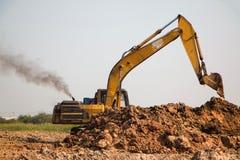 Funzionamento dell'escavatore a cucchiaia rovescia del caricatore Immagini Stock Libere da Diritti