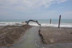 Funzionamento dell'escavatore sulla sabbia e sulla roccia di vangata della spiaggia per l'ambiente di riparazione e fare parete a fotografia stock libera da diritti