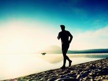 Funzionamento dell'uomo al tempo di penombra della spiaggia Funzionamento dell'atleta del corridore alla spiaggia Siluetta di for Fotografie Stock Libere da Diritti