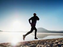 Funzionamento dell'uomo al tempo di penombra della spiaggia Funzionamento dell'atleta del corridore alla spiaggia Siluetta di for Immagini Stock Libere da Diritti