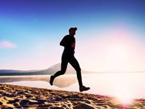 Funzionamento dell'uomo al tempo di penombra della spiaggia Funzionamento dell'atleta del corridore alla spiaggia Siluetta di for Fotografia Stock